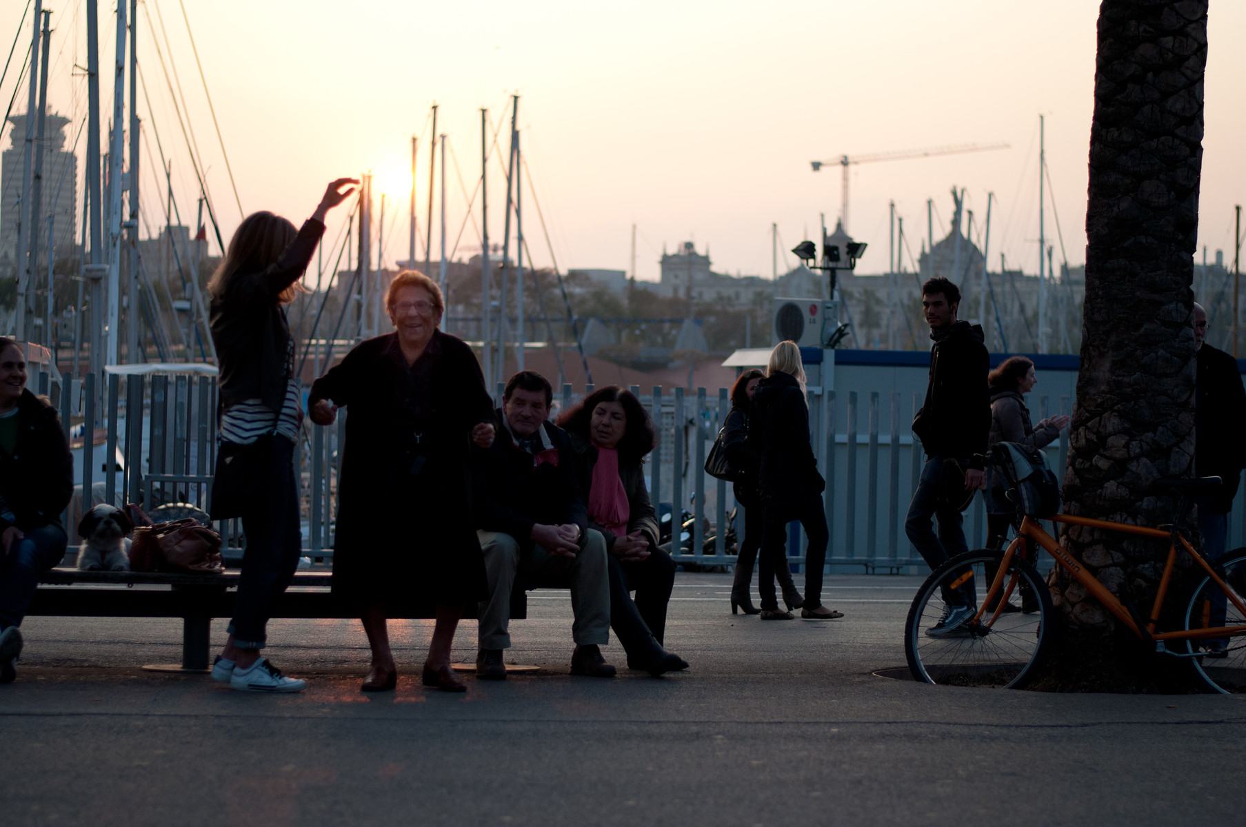 old lady dances while her daughter holds the sun above her head
