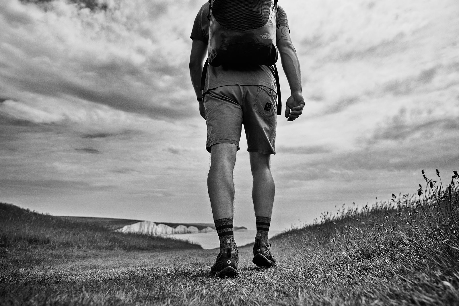 black and white, cliffs, coast, england, feet, hiking, man, moody, sea, seven sisters